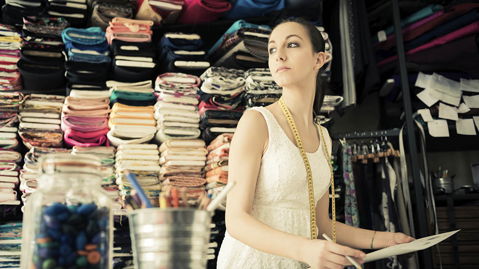 A dressmaker stands in her shop backed by a wall of fabrics
