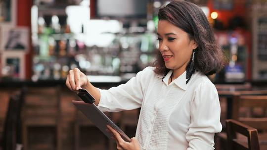 A woman working in a cafe uses a tablet to swipe a credit card