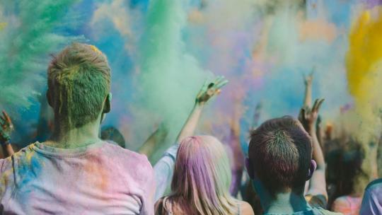 A crowd of people throwing coloured dye into the air shot from behind