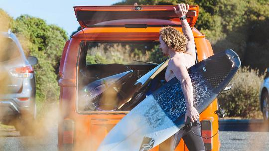 A young man with long hair and a wetsuit carries a surfboard out of a car