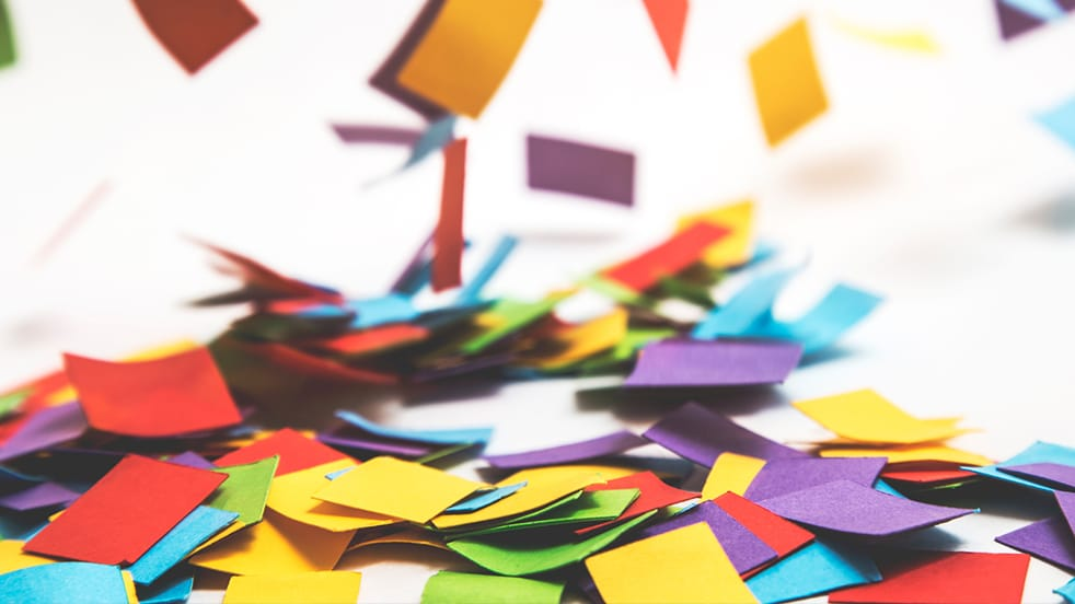 A large amount of multi-coloured post-it notes lying in a large pile on a white floor.