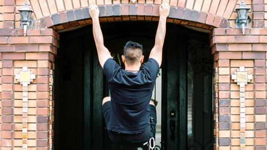 Man doing a chin up against a brick wall