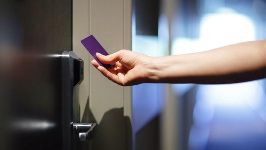 a close up shot of a person using a purple swipe card to enter a hotel room