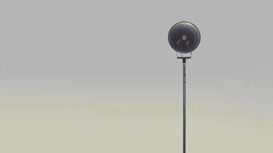a camera on a tall pole is on frame right in front of a grey sky