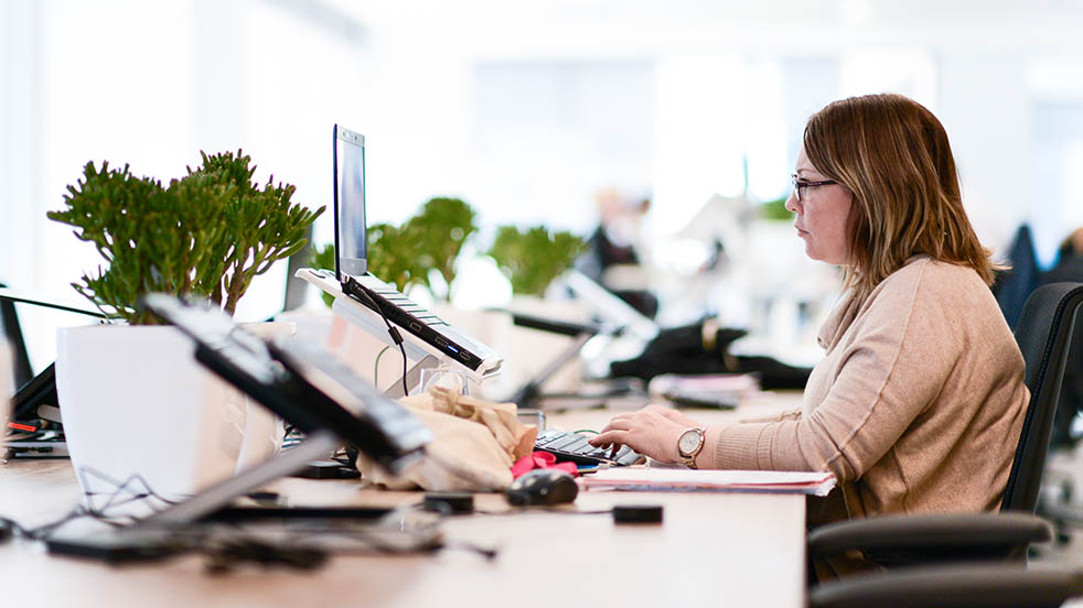 A female worker uses a laptop in a modern office space