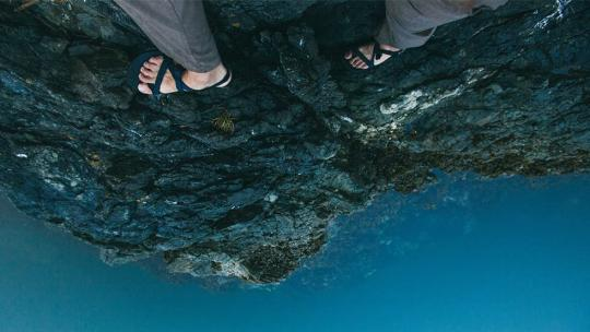 a pair of feet walking precariously along a rocky outcrop