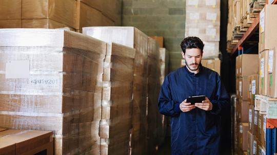 A warehouse worker uses his phone