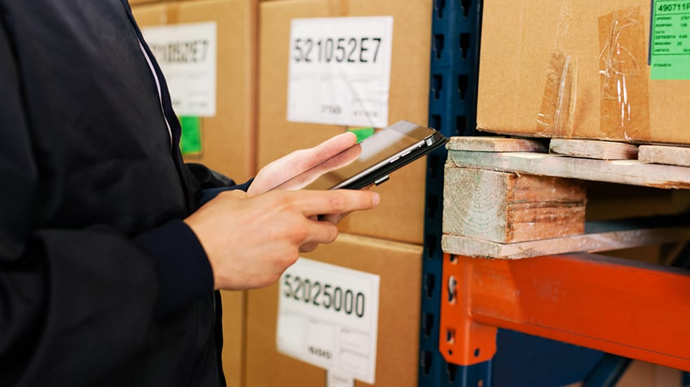 A worker uses a tablet in a wholesale warehouse