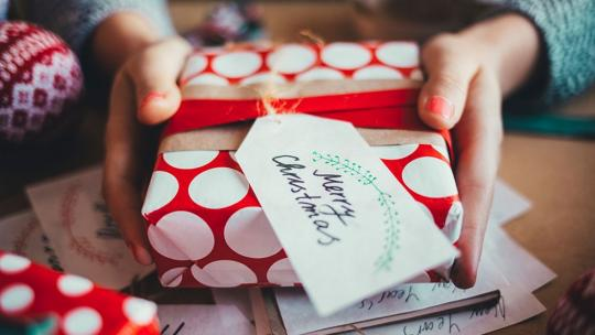 A close up image of a person handing a present covered in red and white spotted paper