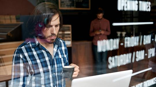 A man drinks a coffee as he works remotely in a café