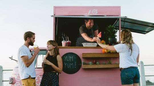 A woman buys an ice cream from a portable stand, while two people chat to one side.