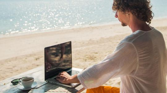 A young man working on a laptop at the beach