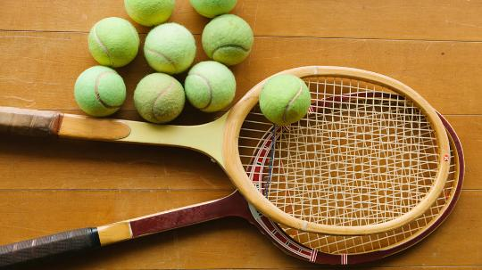 A close up shot of two tennis racquets with a pile of tennis balls