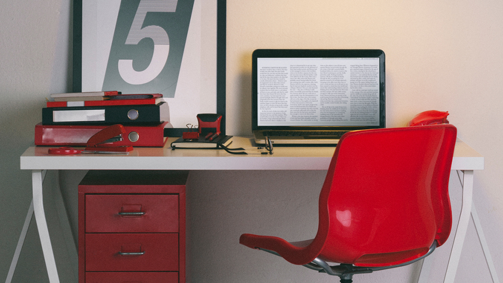 A red desk chair in front of an office desk with laptop.
