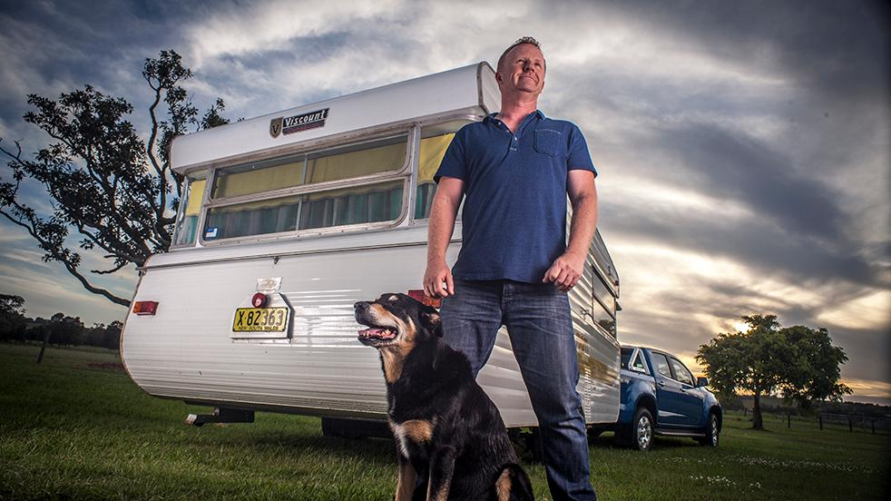 a low angle of a man looking away into the distance in front of a trailer and a dog sitting next to him