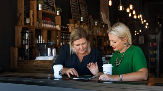 two women meeting in a cafe to work