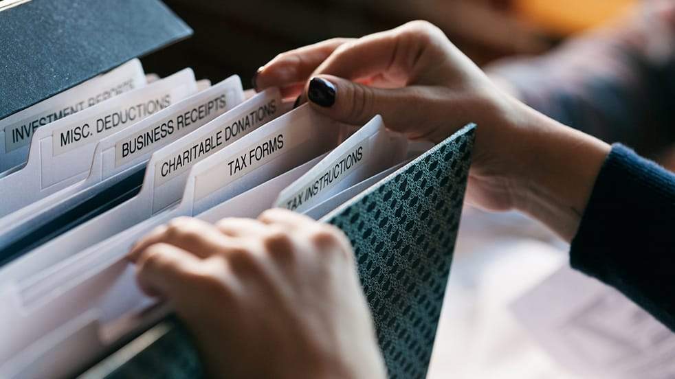A close up photo of a woman rifling through a folder of tax documents.