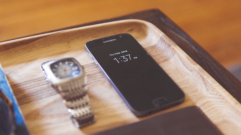 A Samsung Galaxy S7 sitting on a wooden board next to a wrist watch