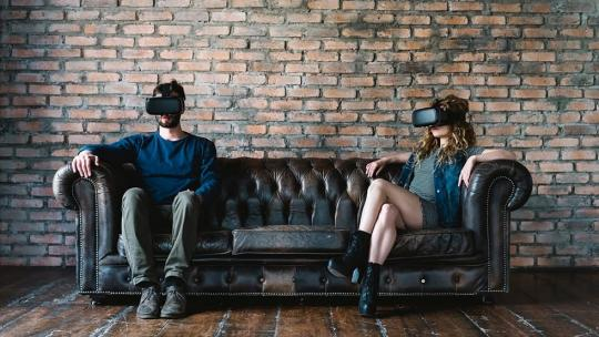 A man and woman sitting on a couch with VR headsets on.