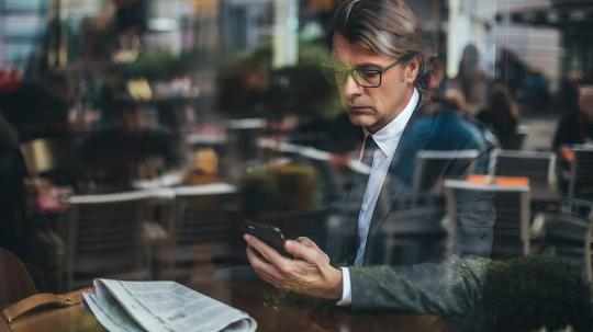 A business man sitting in a cafe working on his mobile phone.