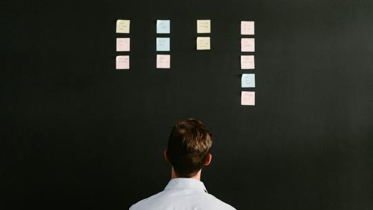 A man looking at a blackboard with post it notes in columns