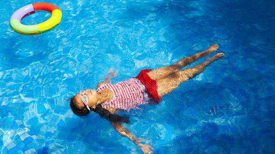 Girl swimming in pool with inflatable ring