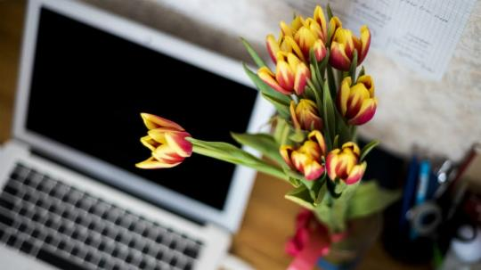 A laptop and vase of flowers sitting on a desk