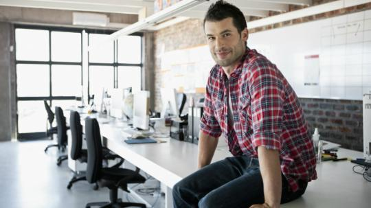 man sitting on desk in warehouse office space