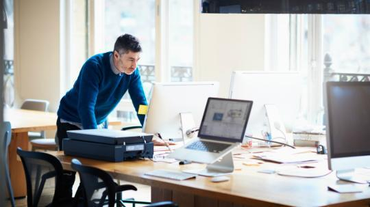 man standing at desk working on computer