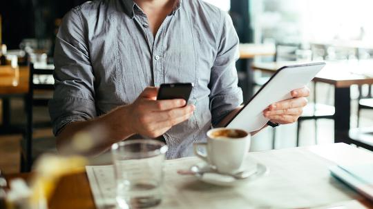 man sitting in cafe with electronic devices
