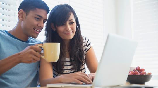 Man and woman drinking tea looking at laptop
