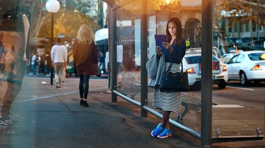 Woman waiting at bus stop whilst working on tablet