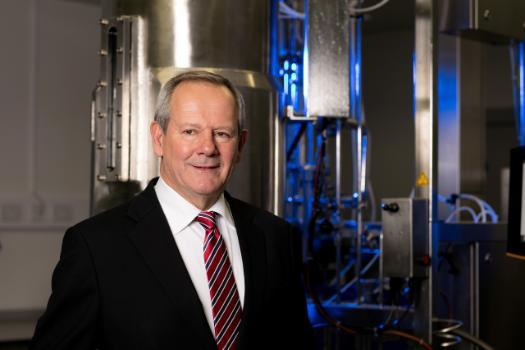 Dr Barry McCleary Telstra Business Award winner standing in front of distillers