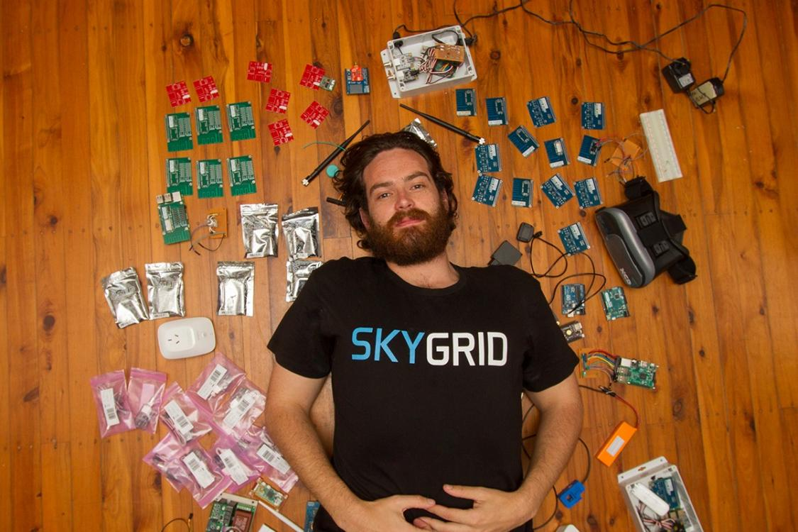 Image shows IoT start-up SkyGrid co-founder Luke Taylor surrounded by computer parts, virtual reality goggles and power cords.