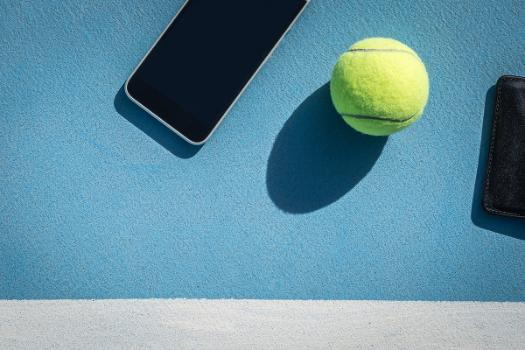 Image shows a smartphone and a tennis ball on a tennis court.