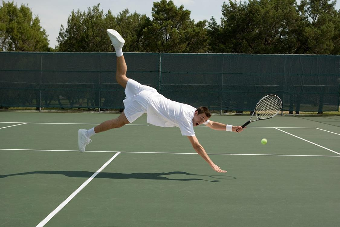 Image shows a man diving for a ball on a tennis court.