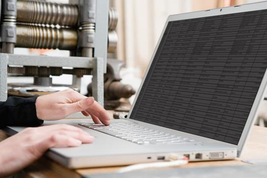 The image shows a laptop with a spreadsheet open on the screen.