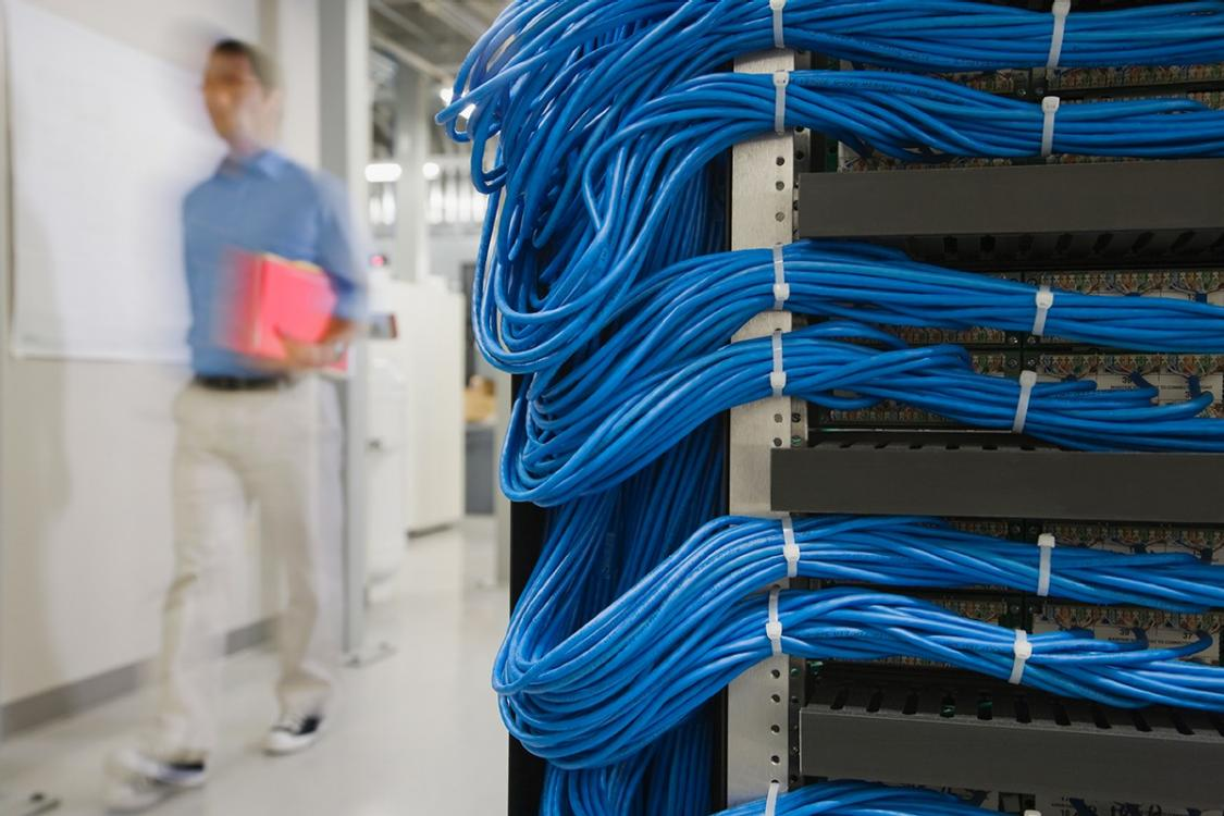 The image shows bundles of server cables and a service person in the background.