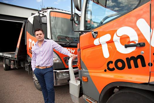 Image shows Dominic Holland, founder of Tow.com.au, standing in front of some of the trucks in his towing fleet.