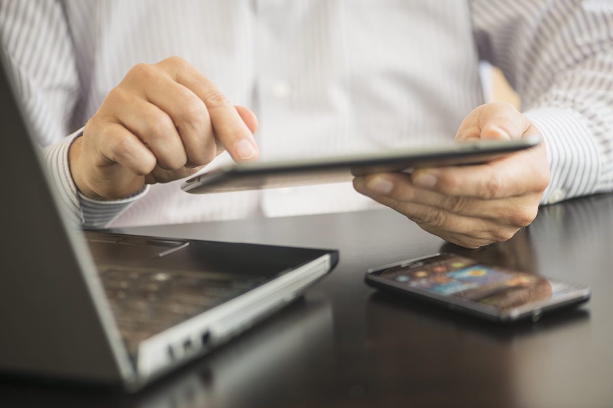 man using a tablet, laptop and smartphone
