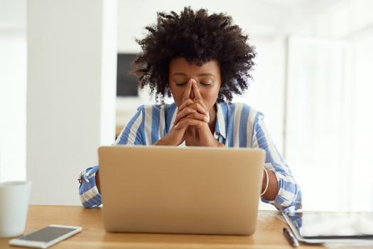 Woman using laptop looking concerned.
