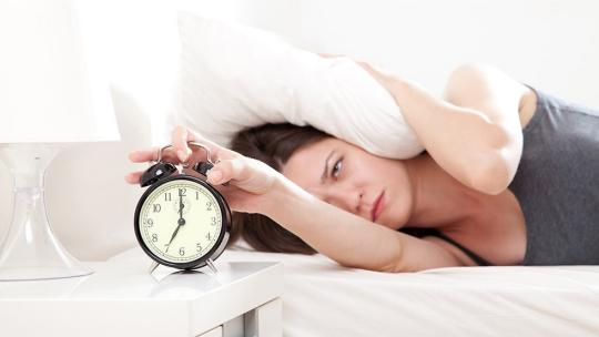 woman in bed switching off her alarm clock