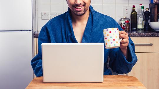 man drinking coffee works from home on his laptop