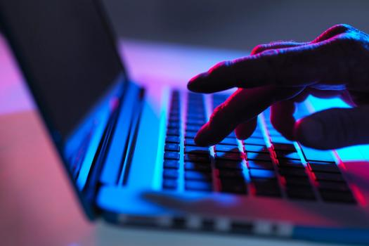 Image shows a close up of silhouetted hand using a laptop in dramatic lighting.