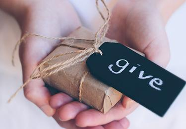 Hands holding a wrapped present with gift tag